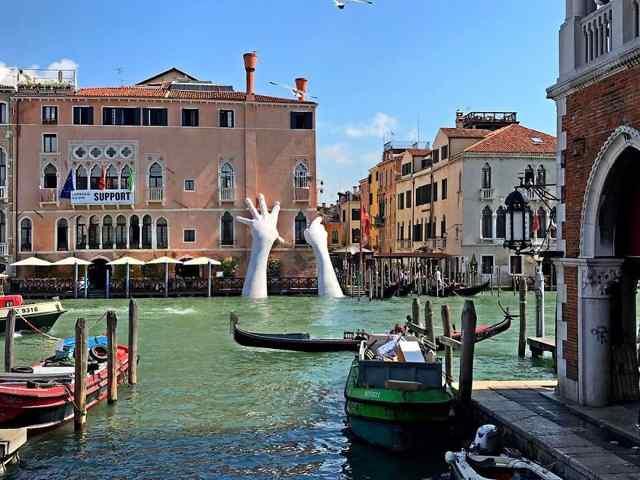 Гигантские руки поднимаются из канала в Венеции, чтобы послать сигнал о изменении климата.