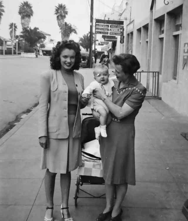 Норма Джин Мортенсон позирует для фото с подругой и ее ребенком (1941)